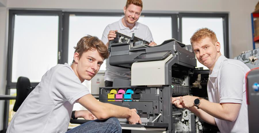 Drei Techniker reparieren und warten einen Drucker von Konica Minolta