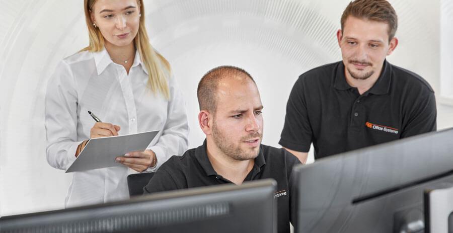 Kundin notiert Anleitung des Mitarbeiters für IT-Systeme vor dem Arbeitsplatz