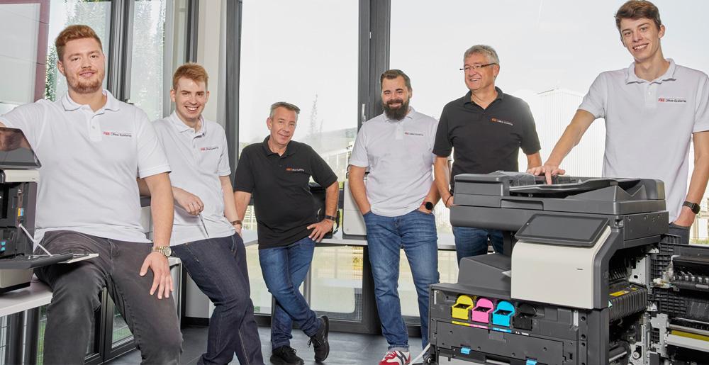Support Team von FBS hinter einem frisch gewarteten Drucker