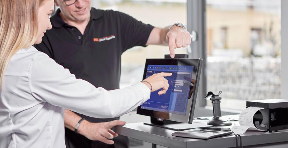 Mitarbeiter erklärt einer Kundin das Kassasystem vor Ort vor dem Monitor