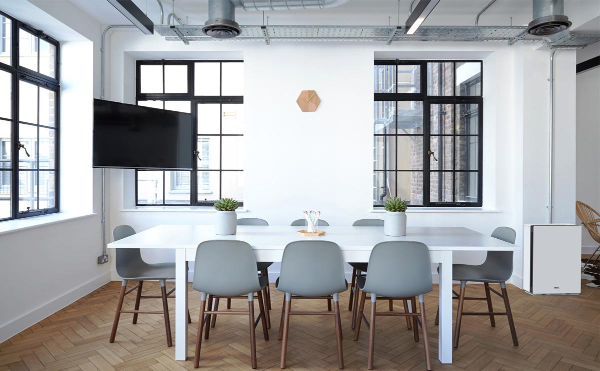 Büro Meeting Raum mit Sesseln und Besprechungstisch, wand-montierter TV für Präsentationszwecke