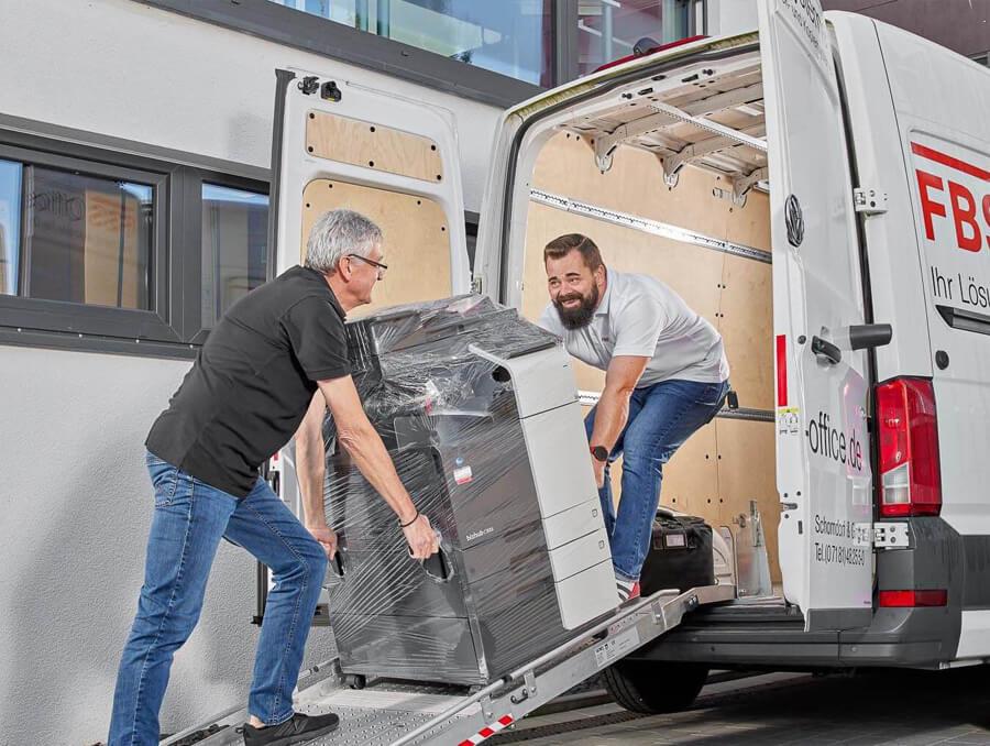 Zwei Mitarbeiter am einladen des Drucker in den Firmenwagen für die Lieferung zum Kunden