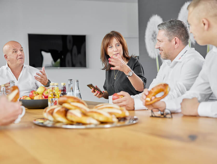 Geschäftsführung am Besprechungstisch mit Jause bei einem internen Meeting
