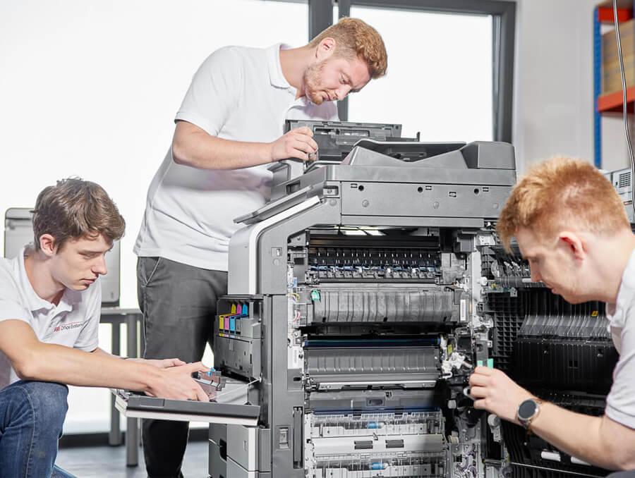 Drei Mitarbeiter führen Service durch und reparieren einen Drucker beim Kunden