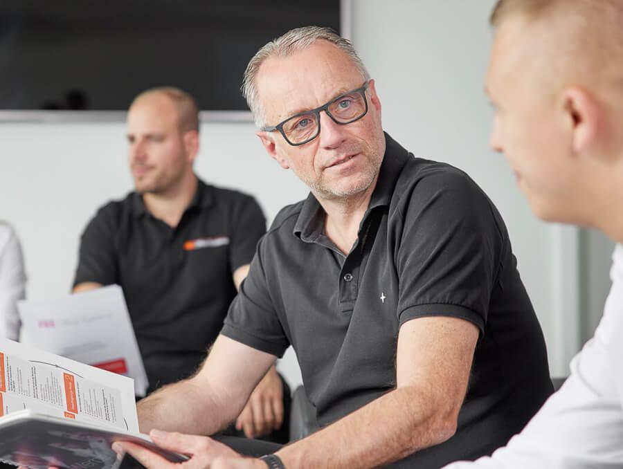 Mitarbeiter im Gespräch über die Drucker und Kopiere mit Broschüre für neue Produkte