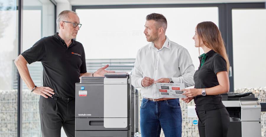 Mitarbeiter erklärt zwei Kunden den Drucker von Konica Minolta
