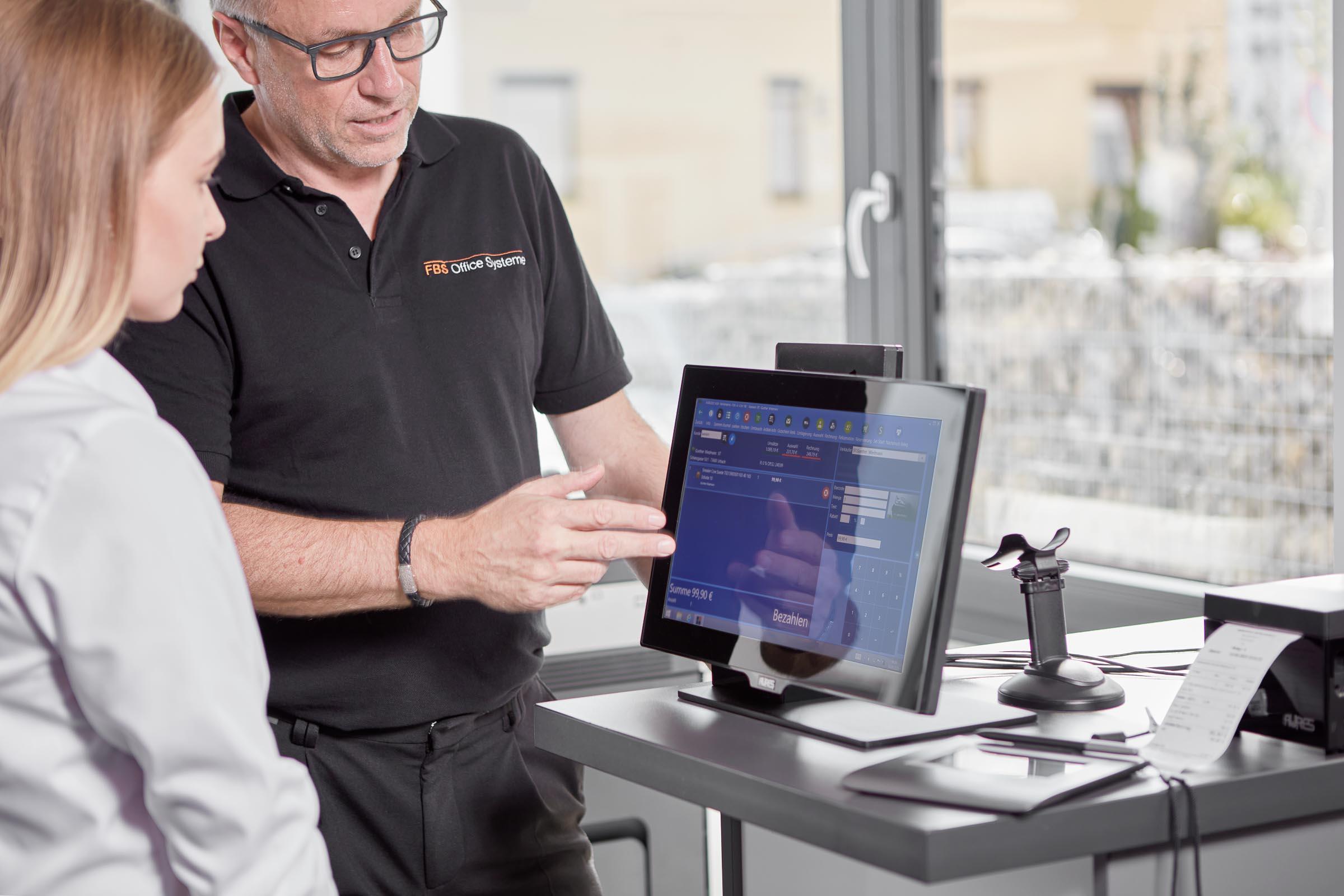 Mitarbeiter erklärt Kunden das Kassasystem am Tablet